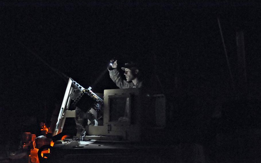 Army Spc. Steven Polack, with the 1st Combined Arms Battalion, 194th Armor, checks his mounted weapon on his MRAP Friday night at Camp Echo, Iraq. The unit arrived there early Wednesday and was escorting a convoy back to Kuwait.