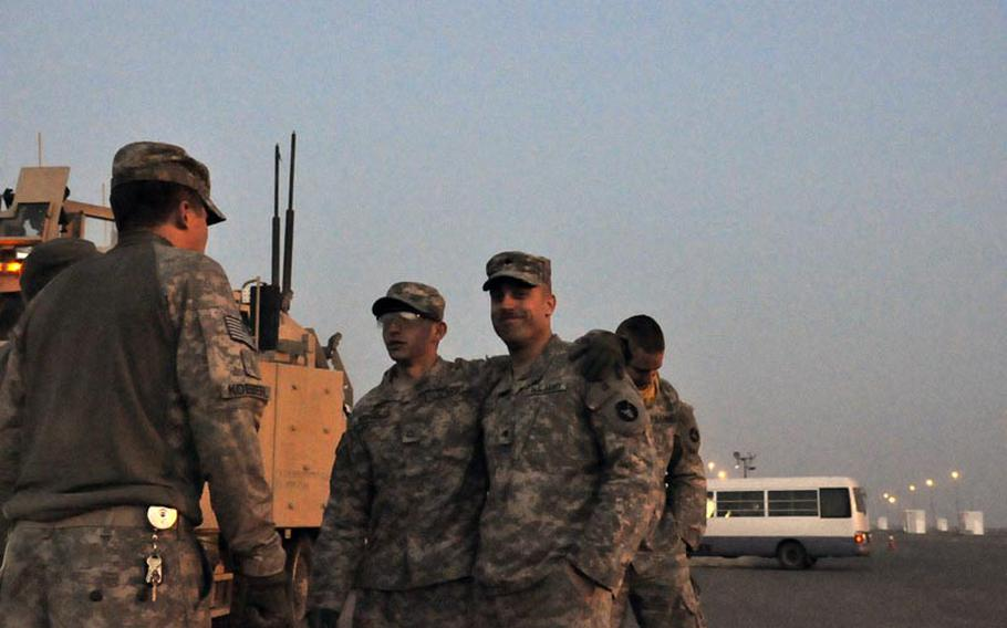 After safely crossing the border from Iraq into Kuwait for the final time Saturday morning, Army Pfc. Todd Wenzel, left, and Spc. Tim Kuechle, and other members of the 1st Combined Arms Battalion, 194th Armor, breathe a sigh of relief and celebrate.