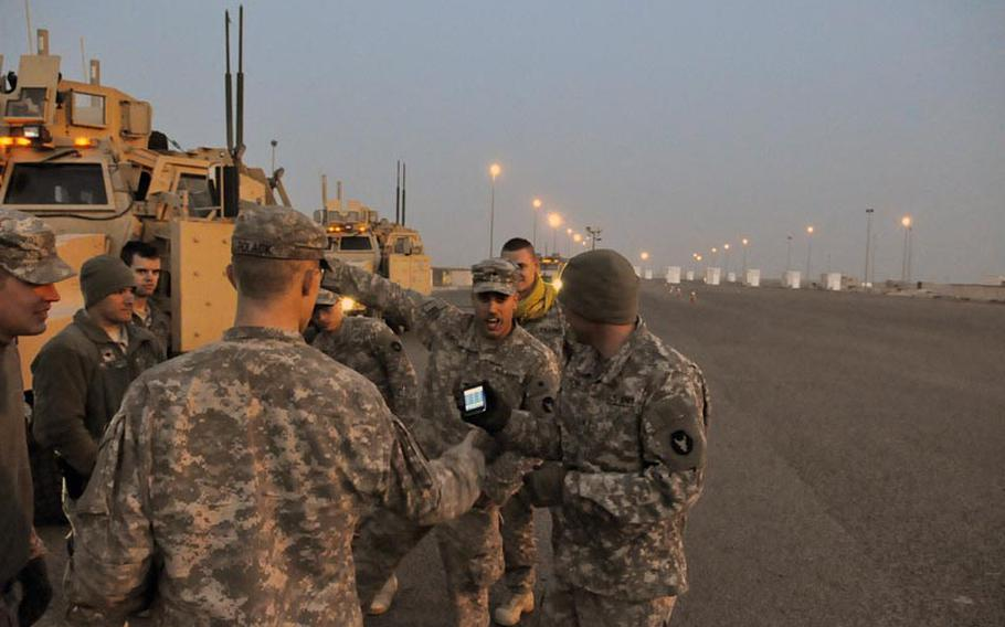 Soldiers with the 1st Combined Arms Battalion, 194th Armor, clown around Saturday morning after safely crossing over from Iraq to Kuwait for the final time. The unit had spent recent months providing security escorts for convoys moving materiel out of U.S. bases in Iraq.