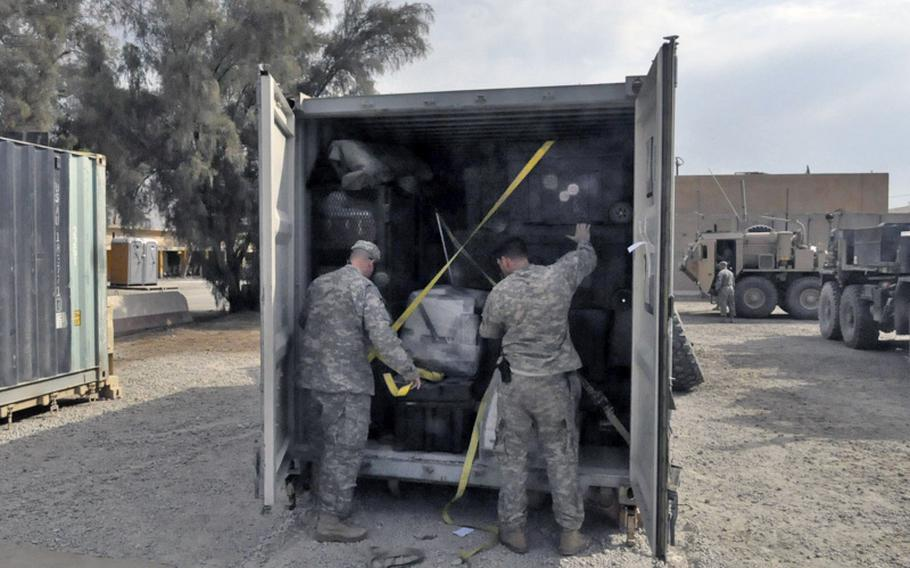 Soldiers with the 1st Cavalry Division's 1st Brigade load some of the last cargo containers at Camp Echo, one of the last U.S. bases to close in Iraq this month. The brigade's community was initially told the soldiers would be coming home early. But a change of plans means most of them will spend the final six months of their tour in Kuwait, which has angered some soldiers and family members.