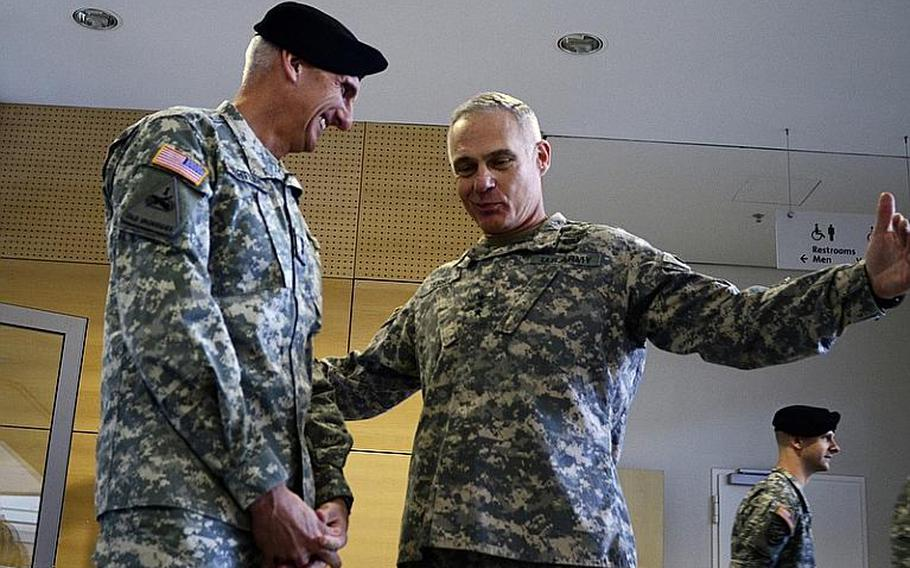 Lt. Gen. Mark P. Hertling, left, commander of U.S. Army Europe and Seventh Army, laughs at an animated Lt. Gen. James L. Terry on Tuesday. Terry assumed command of V Corps on Tuesday during a ceremony at Wiesbaden Army Air Field, Germany.