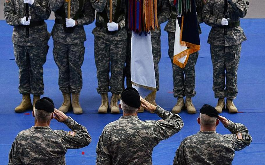 In the foreground, from left, Lt. Gen. James L. Terry, V Corps' incoming commander; Lt. Gen. Mark P. Hertling, commander U.S. Army Europe and Seventh Army; Brig. Gen. Ricky D. Gibbs, outgoing V Corps commander, render honors to the colors during the V Corps change-of-command ceremony at Wiesbaden Army Air Field, Germany.
