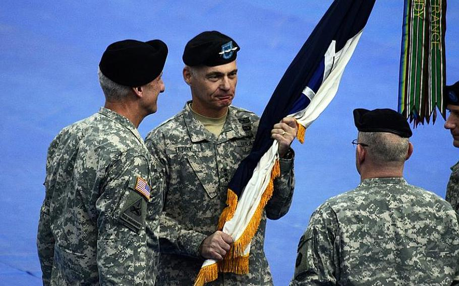 Lt. Gen. James L. Terry, center, the new commander of V Corps, receives the V Corps unit colors from Lt. Gen. Mark P. Hertling, left, commander of U.S. Army Europe and Seventh Army, during the V Corps' change-of-command ceremony Tuesday at Wiesbaden Army Air Field, Germany.