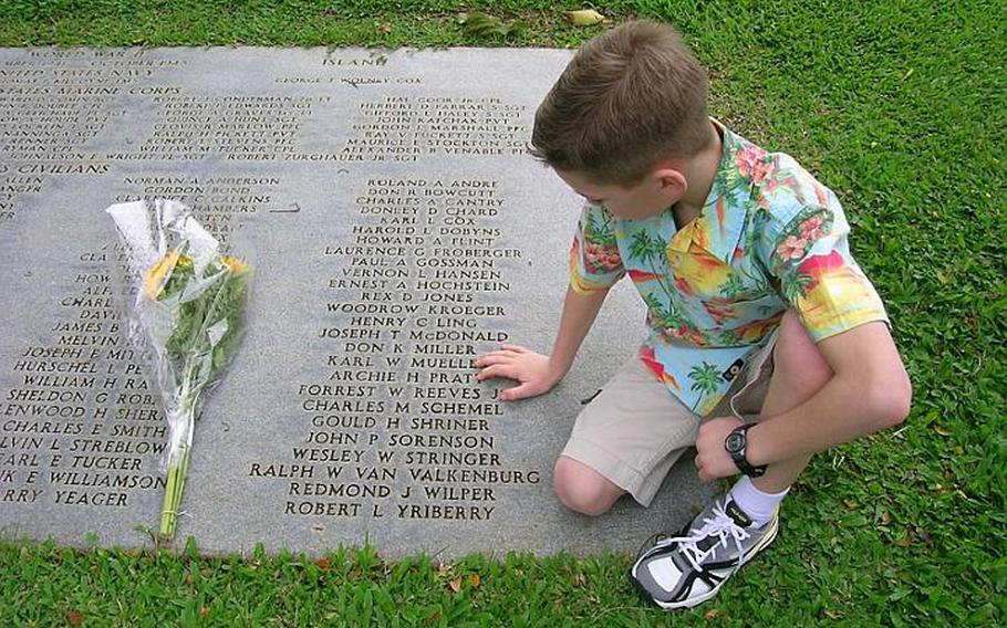 Conor Overholtzer of Sonora, Calif. gingerly touches the name of his great-grandfather, Art Pratt, on the plaque marking the group gravesite of the Wake 98 and others who were recovered from Wake Island but never identified at the Punchbowl National Cemetery of the Pacific, located on Oahu, Hawaii.