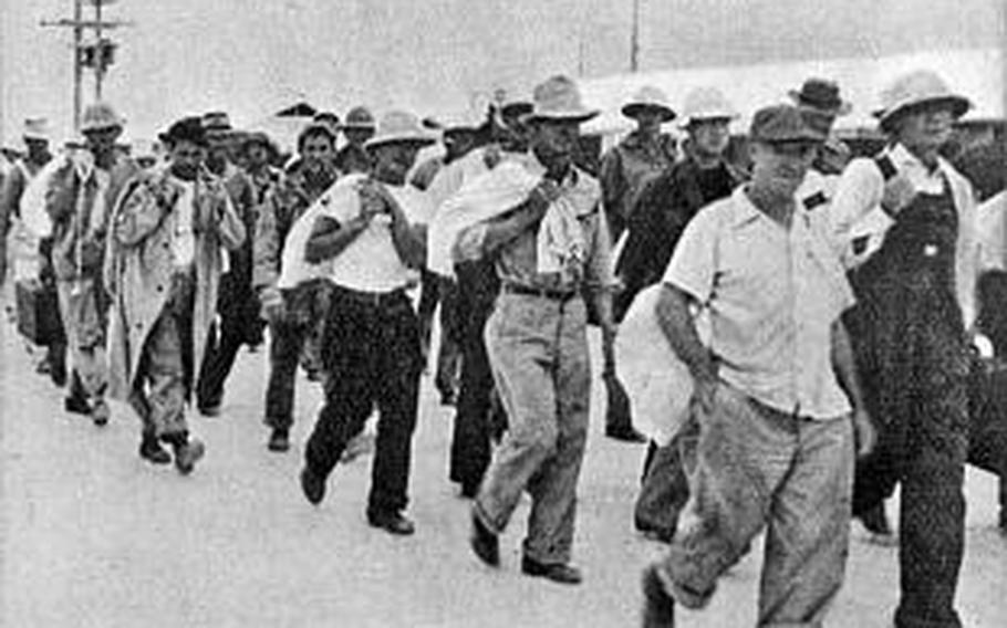 Civilian contractors are marched off to captivity after the Japanese captured Wake. Some, deemed important by the Japanese to finish construction projects, were retained there. Fearing a fifth column rising, the Japanese executed 98 contractors in October 1943, an atrocity for which atoll commander, RAdm Shigematsu Sakaibara, was hanged after the war.