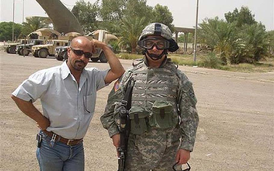 Staff Sgt. Ahmed Altaie, right, poses for a photo with an unknown person at the Swords of Q??disiyyah monument in Baghdad.