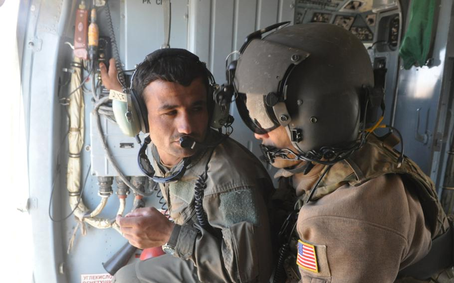 Afghan Air Force recruit Abdul Razeq, left, talks with U.S. Air Force Staff Sgt. Christopher Morford during a training flight near Shindand Air Base in Herat province.