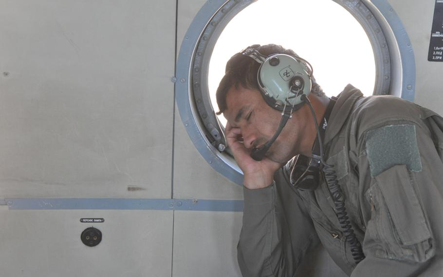 Abdul Razeq, training to become a helicopter crew chief with the Afghan Air Force, dozes briefly during a training flight near Shindand Air Base in Herat province.
