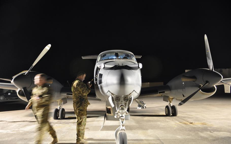 Army National Guard 1st Lt. Daniel Fackel, right, and Maj. Darrell Rasor prepare a King Air plane with electronic surveillance technology at Kandahar Air Field for a flight. The communications electronic attack with surveillance and reconnaissance (CEASAR) technology attached to the plane can intercept and jam communications miles below.