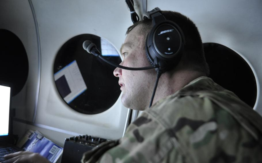 First Lt. Daniel Fackel of with the Virginia National Guard listens to intercepted conversations while flying over a ground operation in Helmand province.
