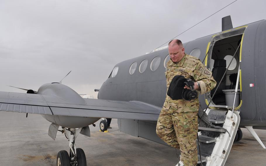 Army National Guard Maj. Darrell Rasor walks off a King Air plane after a surveillance mission over Helmand province.