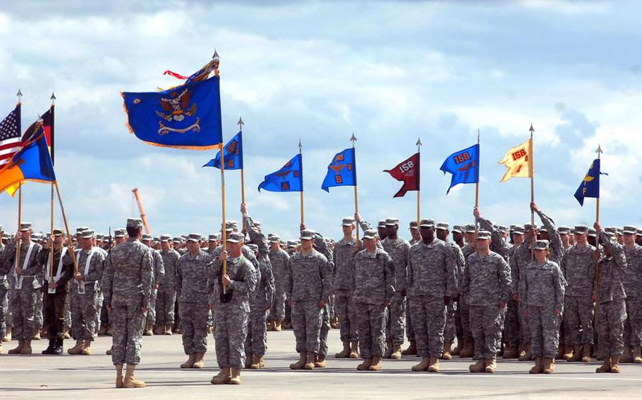 Soldiers with the 12th Combat Aviation Brigade stand at attention during the colors casing ceremony for the brigade on April 20, 2012, in Katterbach, Germany. The brigade's units are deploying to Afghanistan and Kuwait for a 10-month tour.