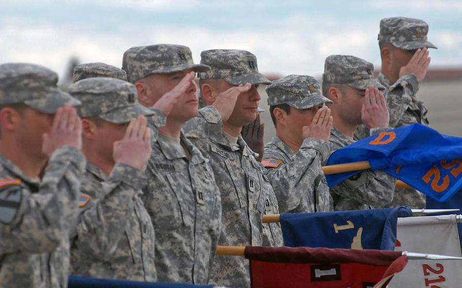 Soldiers with the 12th Combat Aviation Brigade salute as they pass the reviewing stand at a colors casing ceremony for the brigade on April 20, 2012, in Katterbach, Germany. The brigade's units are deploying to Afghanistan and Kuwait for a 10-month tour.