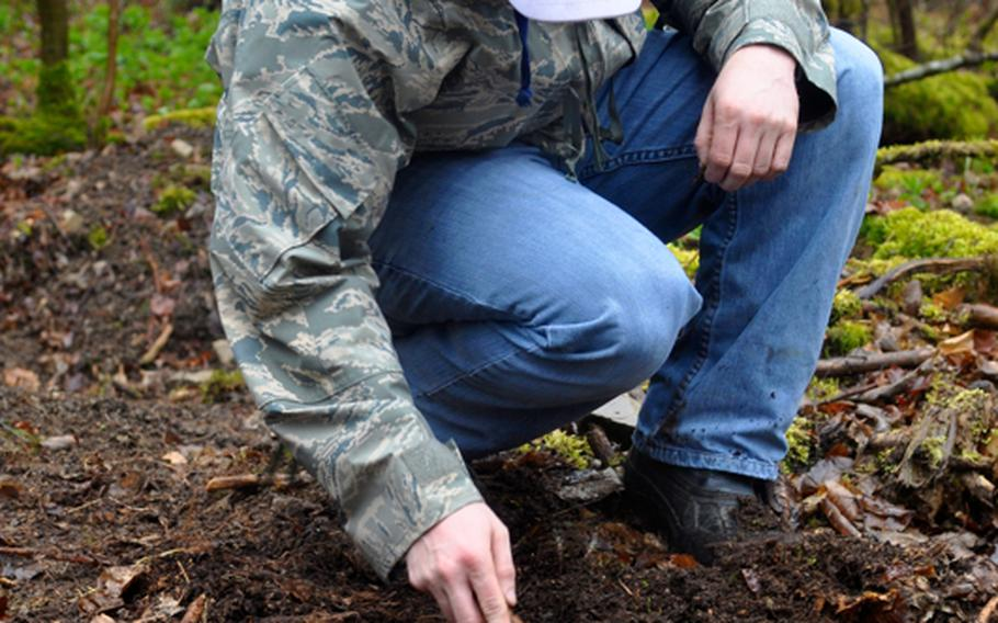 Ray Vinton, a Spangdahlem-based airman and metal detector enthusiast, sifts through the dirt of what is believed to be a World War II crash site of an American bomber near the town of Grafenau, Germany, on April 5, 2012.