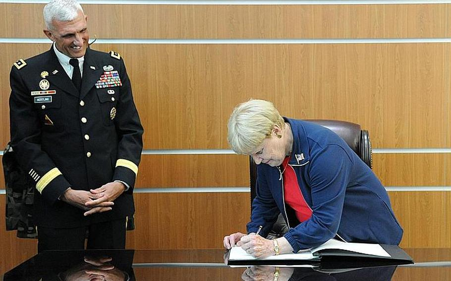 As U.S. Army Europe commander Lt. Gen. Mark Hertling watches, Joan Shalikashvili, widow of the former Chairman of the Joint Chiefs of Staff Gen. John Shalikashvili, signs the guest book on a desk used by her husband. Earlier Thursday, they had dedicated the new U. S. Army Europe mission command center in Wiesbaden, Germany, to the late general.
