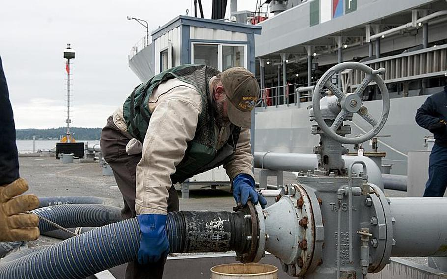 David Riggs, from Fleet Logistic Center Puget Sound, Wash., secures a fueling hose during a biofuel transfer to the USNS Henry J. Kaiser on July 13, 2012. The ship took on 900,000 gallons of a 50/50 blend of biofuels and petroleum-based fuel, and is now fueling ships participating in the Great Green Fleet demonstration during the Rim of the Pacific exercise in Hawaii.