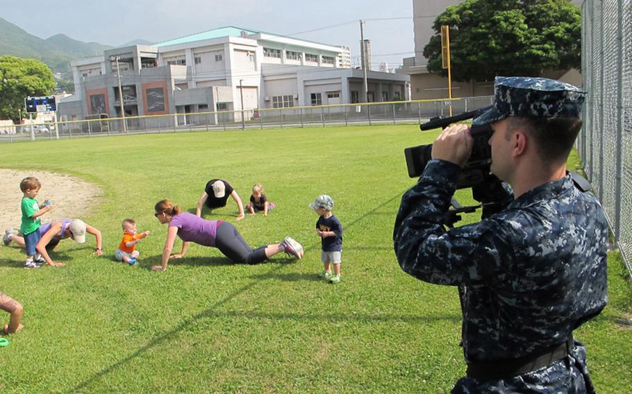 Petty Officer 3rd Class Scott Bourque mans the camera during a May 2012 shoot for the American Forces Network at Nimitz Park, Sasebo Naval Base, Japan. Borque was shooting footage for an ad for Baby Boot Camp, a parent-and-child exercise program.