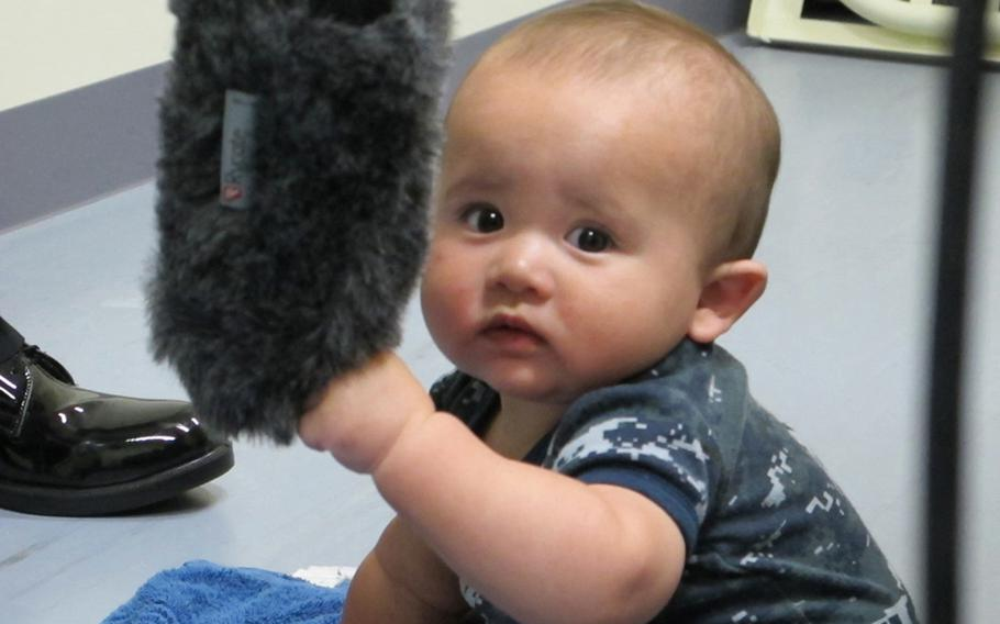 Brandon Monckton investigates the boom mike while making his TV debut in May 2012 in an AFN commercial for a baby-and-parent fitness program at Sasebo Naval Base, Japan.