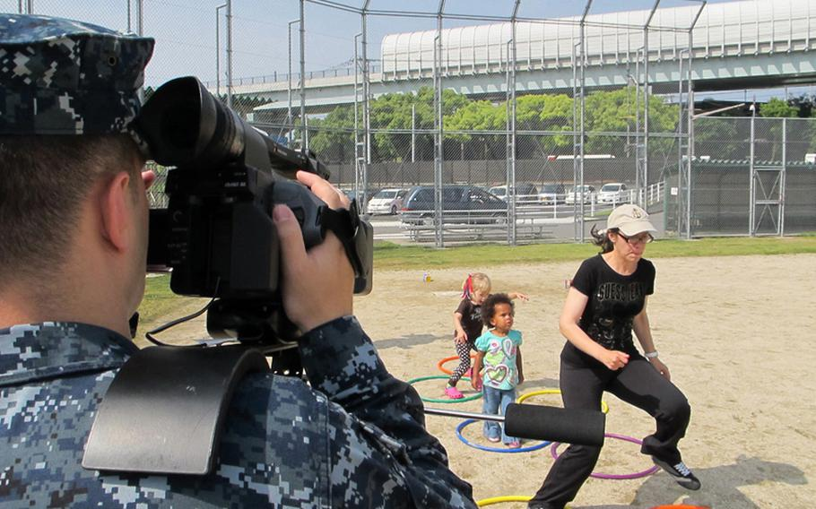 Petty Officer 3rd Class Scott Bourque mans the camera during a May 2012 shoot for the American Forces Network at Nimitz Park, Sasebo Naval Base, Japan. Bourque recorded parents and their children at a fitness program called Baby Boot Camp for a humorous spot to spread the word about the program.