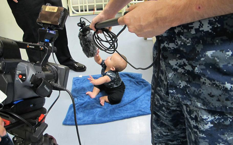 Brandon Monckton, son of Petty Officer 2nd Class Michael Monckton, makes his television debut in an AFN  spot for Baby Boot Camp, with his father playing a drill instructor, in May 2012.