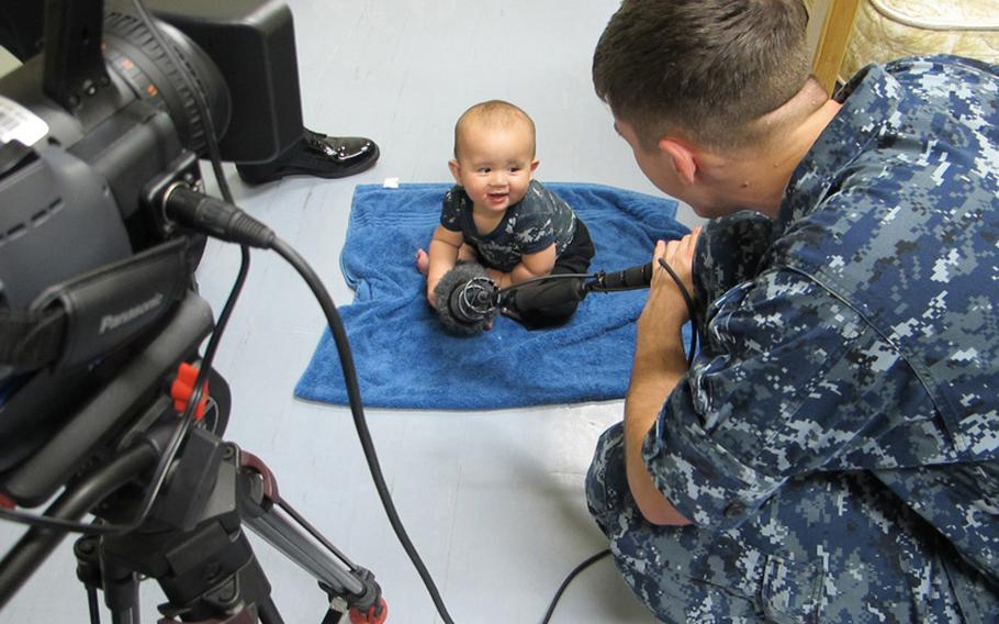 Seaman Greg House laughs with Brandon Monckton, son of Petty Officer 2nd Class Michael Monckton, as Brandon makes his television debut in an AFN spot for Baby Boot Camp, a baby-and-parent fitness program at Sasebo Naval Base.