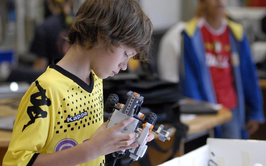 """Mason Payeur, who will be going into the seventh grade at Wiesbaden Middle School in Germany, makes adjustments to his robot at the Robotics Summer Day Camp at Wiesbaden High School earlier this month. """"It's been real fun, best camp I've been to this summer,"""" Mason said."""