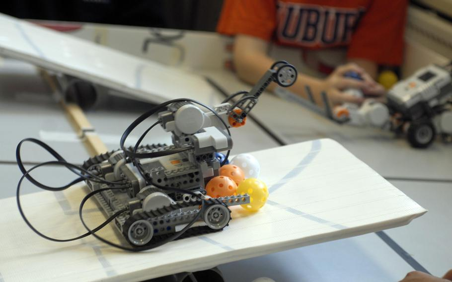 A robot attempts to cross a teeter-board bridge and dump pingpong balls into an opponent's territory at the Robotics Summer Day Camp at Wiesbaden High School in Germany earlier this month.