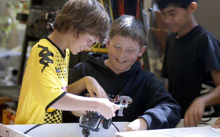 Mason Payeur, left, who will be in the seventh grade this upcoming school year at Wiesbaden Middle School in Germany, and Max Johnson, who will be entering the eighth grade at Wiesbaden Middle School, examine a robot during the recent Robotics Summer Day Camp at Wiesbaden High School.