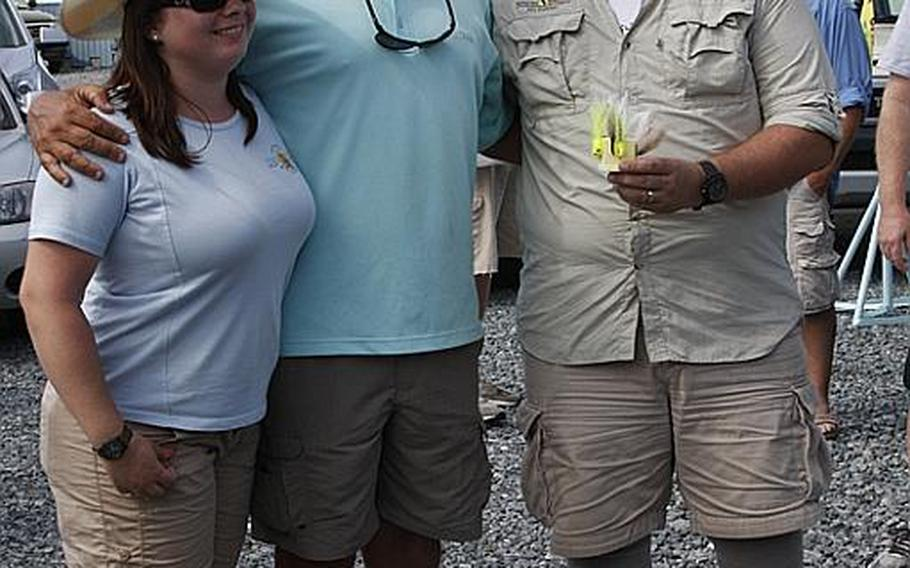Chris Frost, an Air Force veteran, and his wife, Cathy, an Army veteran, pose with their captain for the day, Richie Gaines, center, after Project Healing Waters' Stars and Stripers tournament last month in Chester, Md. Gaines was one of more than a dozen local fishermen and charter captains who volunteered their boats for the event.