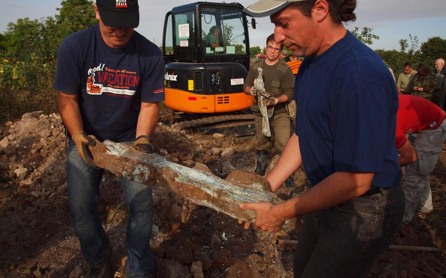 Volunteers carry a piece of metal recovered from the site of a World War II plane crash outside Laumersheim, Germany.