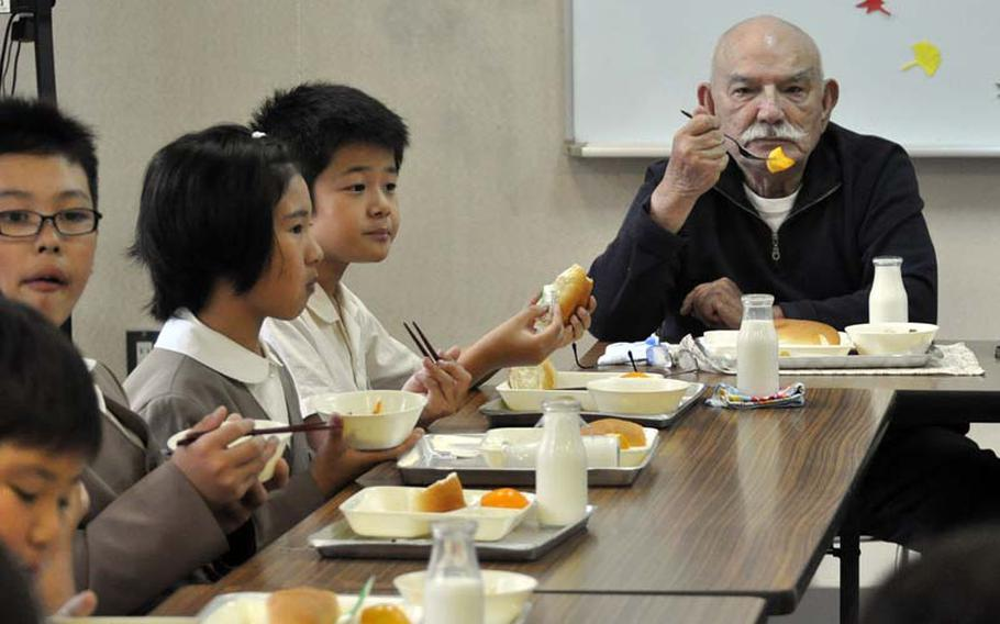 """George Summers, a former POW in Japan, eats lunch with children at Takami Elementary School near the former Sakurajima concentration camp. The students asked Summers and two other former POWs questions about war and the atom bomb. """"War is the curse of the world,"""" Summers told them."""