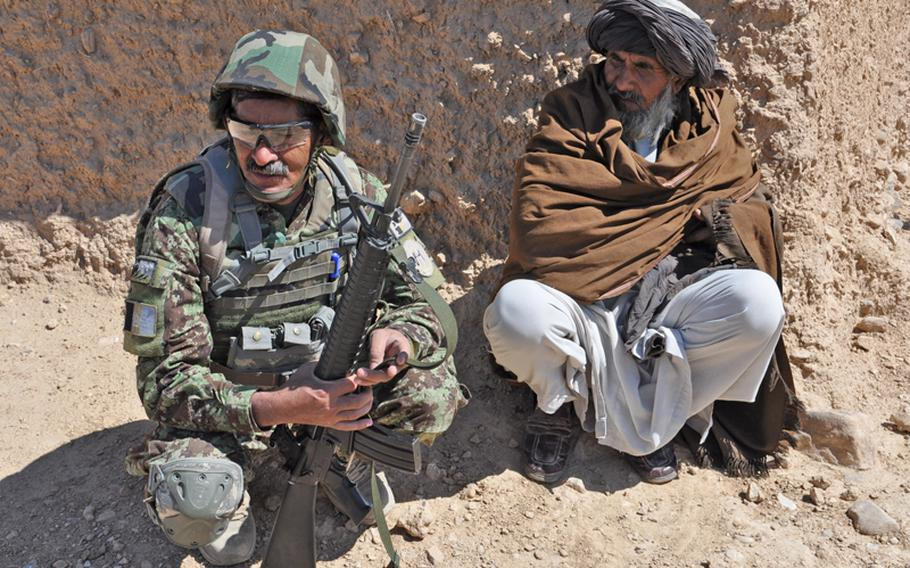 An Afghan soldier crouches with a villager in Kandahar province in April. Plans to reduce the Afghan national security forces by one-third have some worried that putting so many military-trained men out of work could be a boon for insurgent recruitment.