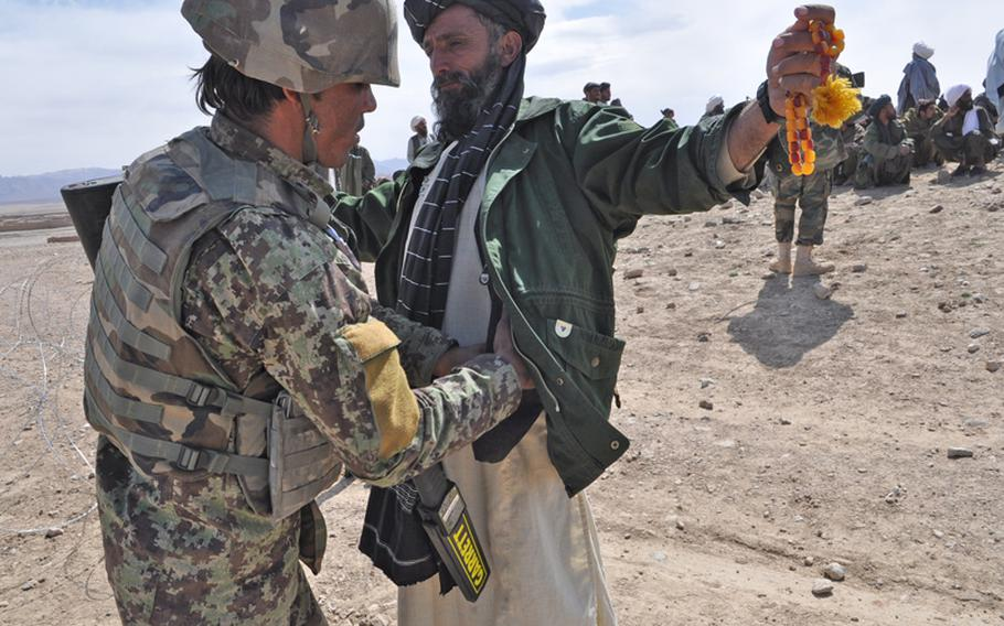 An Afghan soldiers searches a man before a meeting in Kandahar province in April. The U.S. plans to cut the size of the Afghan national security forces by about 120,000 soldiers over the next five years, a move some worry could provide insurgents with recruits.