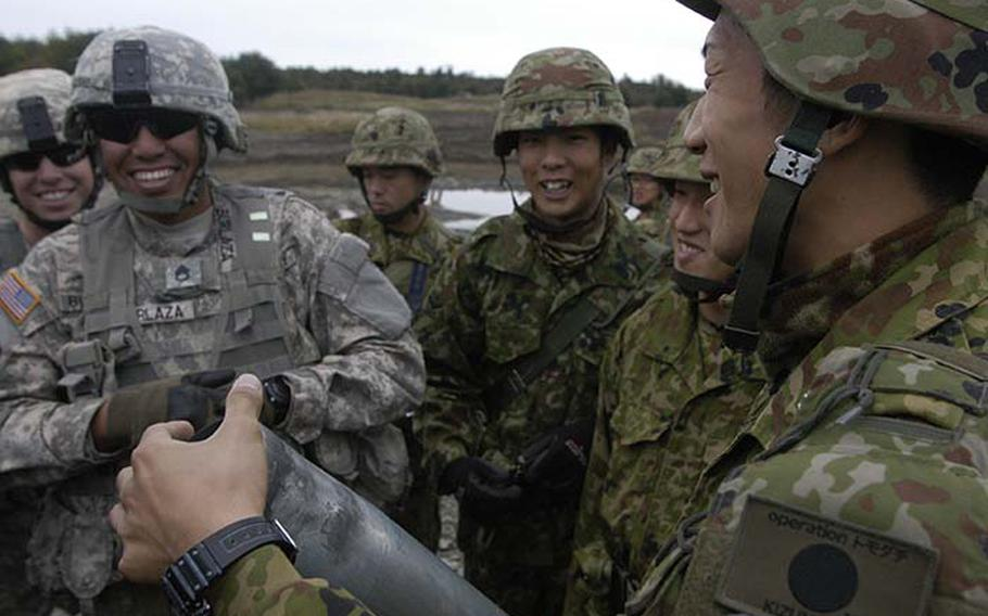 Staff Sgt. Sancho Burlaza, left, jokes with Japanese soldiers Tuesday during exercise Orient Shield as they pass around a 105 mm shell casing fired from the Stryker Mobile Gun System. The 15-day exercise focuses not only on training but also camaraderie among the 1,350 American and Japanese soldiers who are participating.