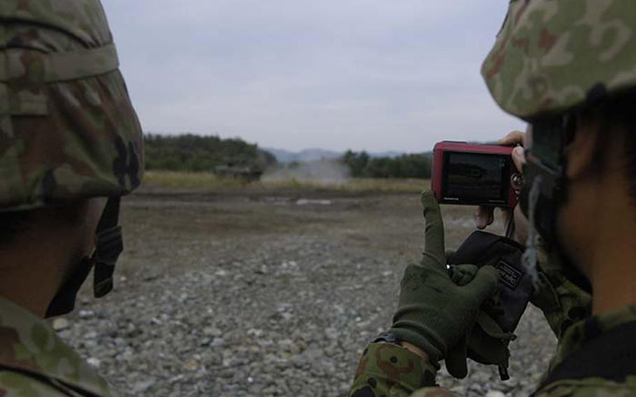 A Japanese soldier takes a photo of the Stryker Mobile Gun System on Tuesday during exercise Orient Shield, a 15-day U.S.-Japan army exercise at Aibano Training Area near Kyoto.