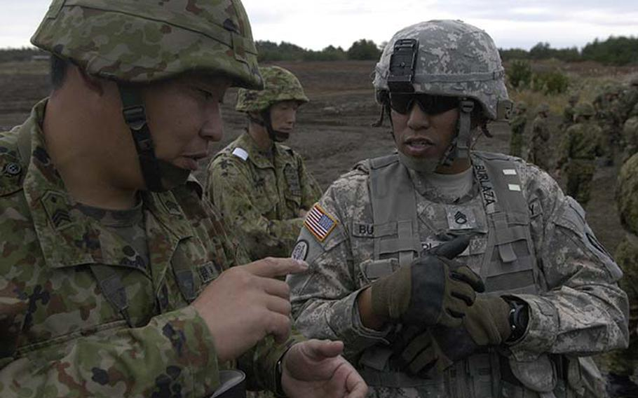 Staff Sgt. Sancho Burlaza talks with a Japanese noncommissioned officer Tuesday during exercise Orient Shield at Aibano Training Area, about an hour northeast of Kyoto. Roughly 750 soldiers, most from the 1st Battalion, 14th Infantry Regiment, 25th Infantry Division out of Hawaii, are participating alongside 600 Japanese troops during the 15-day exercise.