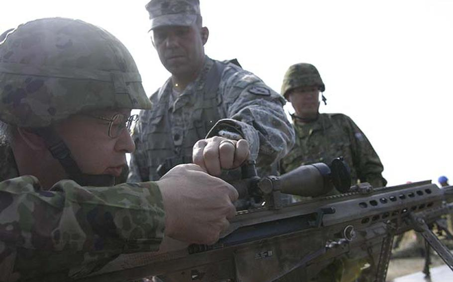 Lt. Col. Jonathan Larson, commander of 1st Battalion, 14th Infantry Regiment out of Hawaii, helps Lt. Gen. Goro Matsumura, Japan?s 10th Division commander, adjust the site on a sniper rifle Tuesday during exercise Orient Shield.