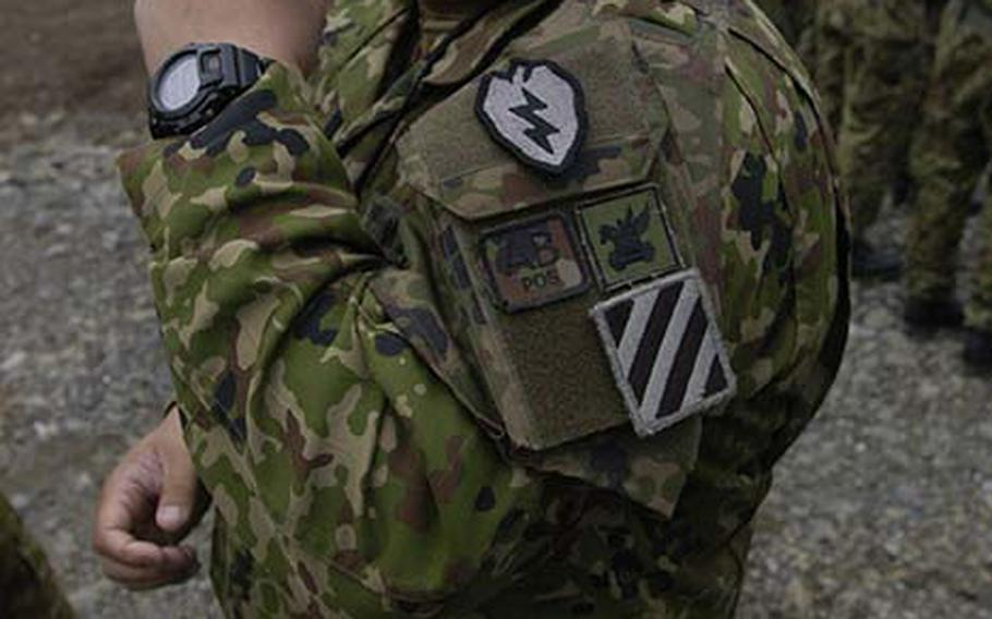 A Japanese soldier shows off a patch he received from a U.S. soldier Tuesday during Orient Shield, a 15-day U.S.-Japan army exercise at Aibano Training Area near Kyoto.