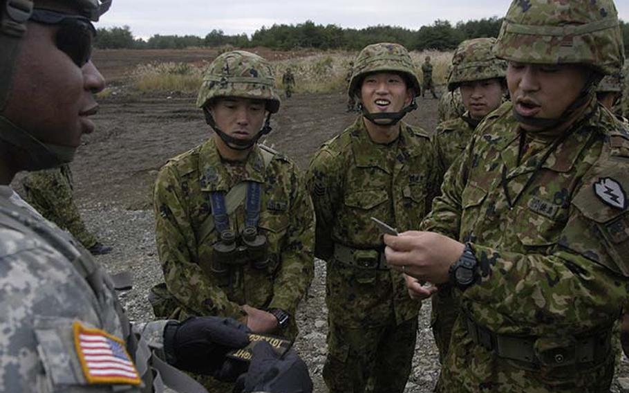 Sgt. DeAndre Bobo exchanges patches with a Japanese soldier Tuesday during Orient Shield, a 15-day U.S.-Japan army exercise at Aibano Training Area near Kyoto. The 15-day exercise focuses not only on training, but on camaraderie among the 1,350 American and Japanese soldiers who are participating.