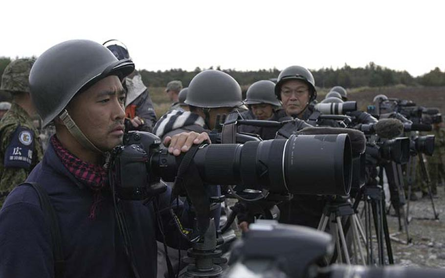 """A Japanese photographer pauses during a demonstration of the U.S. Stryker Mobile Gun System on Tuesday at Aibano Training Area during exercise Orient Shield, which broke down after firing only three of several dozen rounds it was supposed to shoot. The malfunction itself wasn't good, but it was beneficial for the Japanese to see that """"things don't always go according to plan,"""" said U.S. Army Japan spokesman Maj. Randall Baucom."""