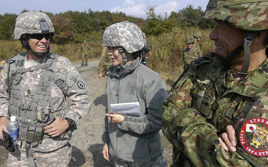 Command Sgt. Maj. Richard Seymour, left, from the 1st Battalion, 14th Infantry Regiment, 25th Infantry Division out of Hawaii, jokes with his counterpart from Japan?s 33rd Infantry Regiment,  Command Sgt. Maj. Toshihiro Shimizu, right.