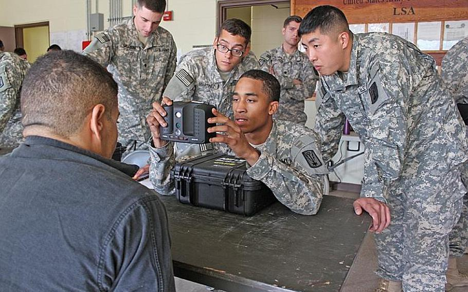 """Soldiers with the 524th Military Intelligence Battalion collect biometric data from a mock North Korean """"detainee"""" using Handheld Interagency Identity Detection Equipment during the recent Northern Vigilance exercise at Camp Carroll. The detainee's facial photo, iris scan and fingerprints were compared against a watch list for identification during the intelligence-gathering exercise, which including approximately 200 troops."""