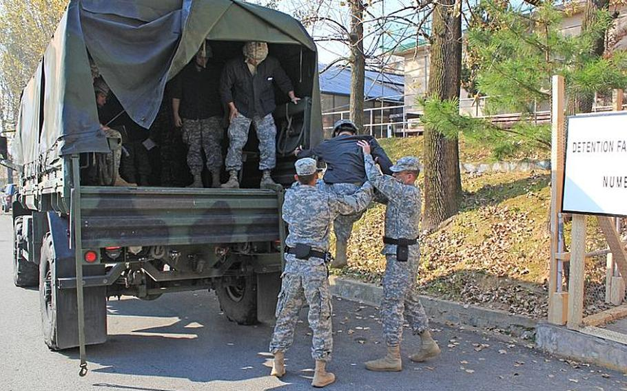 Soldiers from the 94th Military Police Battalion transport mock detainees to a simulated detention facility, a gym at Camp Carroll, during the 524th Military Intelligence Battalion's recent Northern Vigilance exercise. MPs participated to make the intelligence-gathering exercise more realistic.