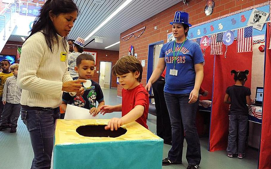 Ramstein Elementary School students drop their ballets in the box after voting in the school's mock presidential election Monday morning.