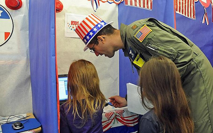 Maj. Andrew Vail helps Ramstein Elementary School students vote at the school's mock presidential election Monday.