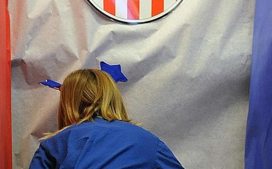 Second-grader Elena Wall, 8, casts her vote at the Ramstein Elementary School's mock election Monday morning.