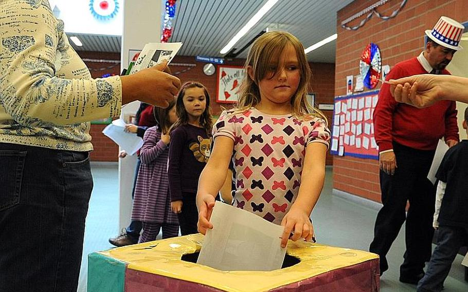 Ramstein Elementary School students drop their ballots in the box after voting in the school's mock presidential election Monday morning.