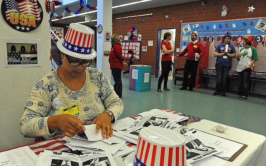 Volunteer Robyn Bostrom counts ballots at the Ramstein Elementary School's mock election on Monday. When some of the voting computers were not working, the students voted the old-fashioned way, marking their choice with a marker on paper.