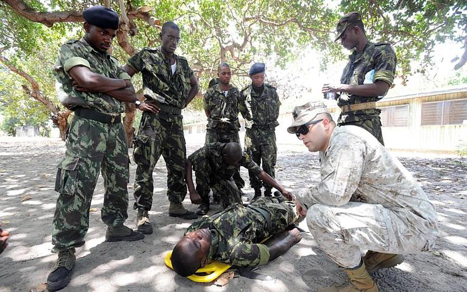Navy Petty Officer 2nd Class Gabriel Fortes, kneeling, a Fleet Marine Force corpsman assigned to U.S. Naval Hospital Naples, Italy, helps marines and sailors from Mozambique and Tanzania practice their medical skills during Exercise Cutlass Express in Tanzania.