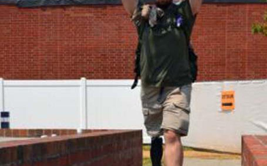 Retired Marine William Gadsby carries a chair over his head to show off his X2 microprocessor knee from Ottobock and BiOM ankle, developed by iWalk. When used together, Gadsby can walk without pain and fatigue with a natural gait like the uninjured.